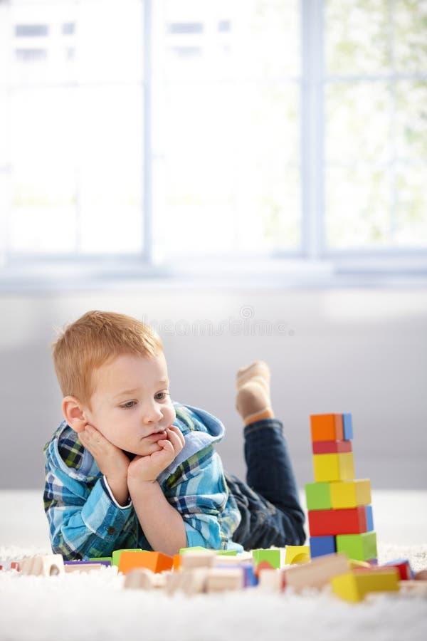Niño pequeño adorable del gingerish con los cubos del edificio foto de archivo libre de regalías