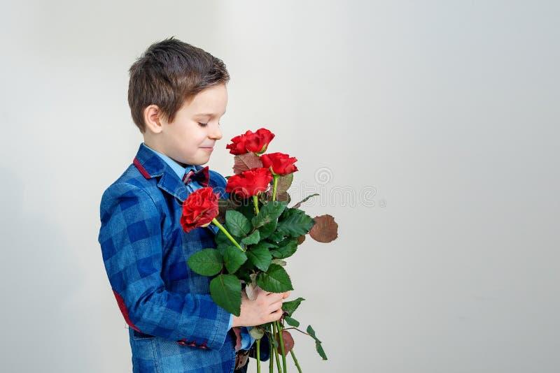 Niño pequeño adorable en traje con el ramo de rosas rojas en un fondo ligero imagen de archivo libre de regalías