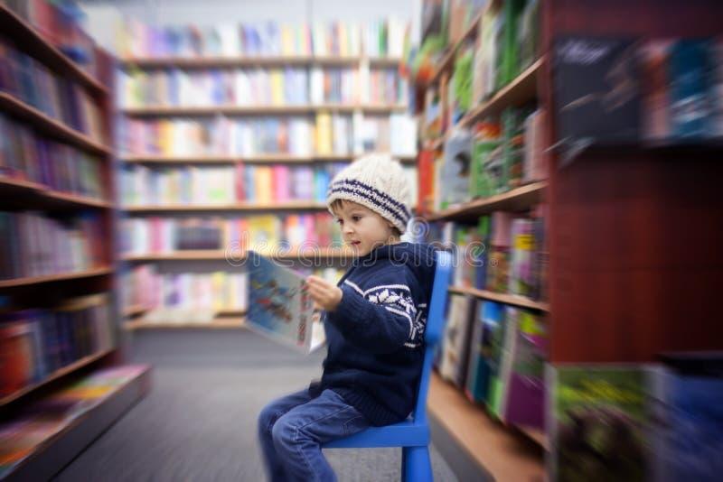 Niño pequeño adorable, sentándose en una librería fotos de archivo