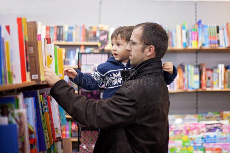 Niño pequeño adorable, sentándose en una librería foto de archivo