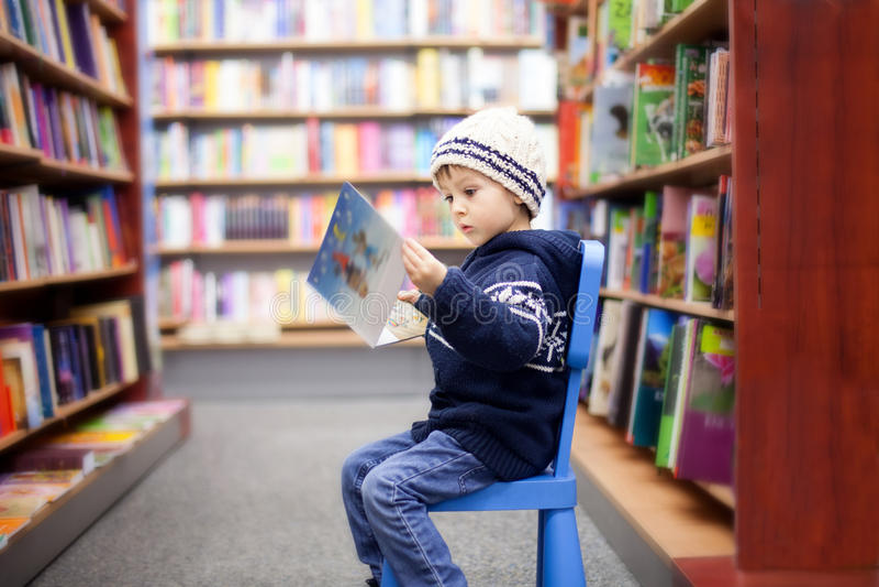 Niño pequeño adorable, sentándose en una librería foto de archivo libre de regalías
