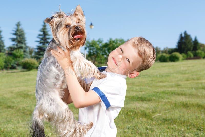 Niño pequeño agradable que sostiene el perro imagen de archivo libre de regalías