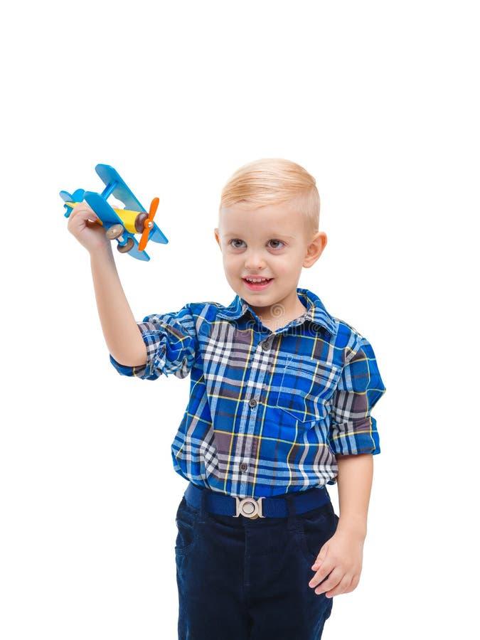 Niño pequeño agudo que juega la diversión con un aeroplano del juguete Aislado en blanco fotografía de archivo libre de regalías