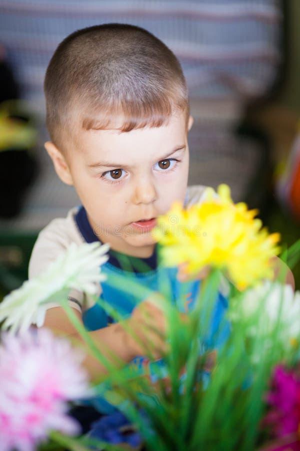 Niño pequeño alegre de la visión superior que toca las flores florecientes hermosas en florero en casa imagenes de archivo