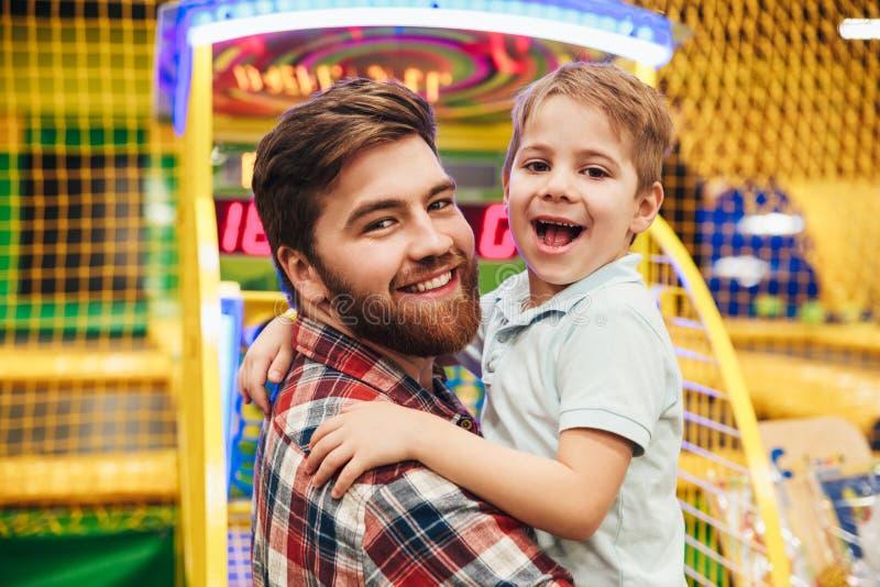 Niño pequeño alegre que se divierte con su papá imagen de archivo libre de regalías