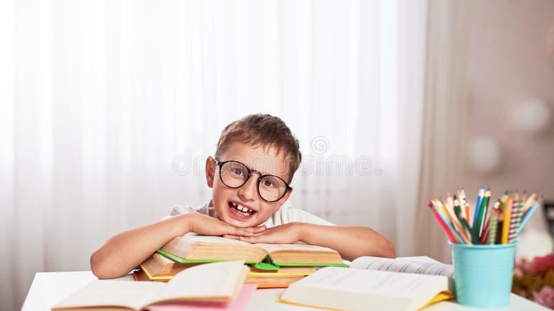Niño pequeño alegre que se sienta en la tabla con los lápices y los libros de texto Alumno feliz del niño que hace la preparación imagenes de archivo