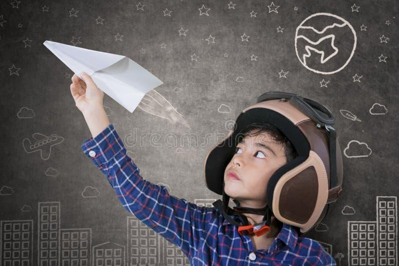 Niño pequeño asiático que juega un aeroplano de papel imagenes de archivo