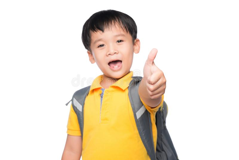 Niño pequeño asiático que le da los pulgares para arriba sobre el fondo blanco imagenes de archivo