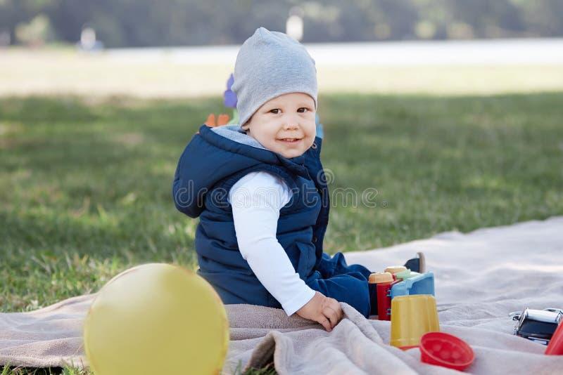 Niño pequeño bonito que juega con un coche del juguete que se sienta en el césped fotografía de archivo