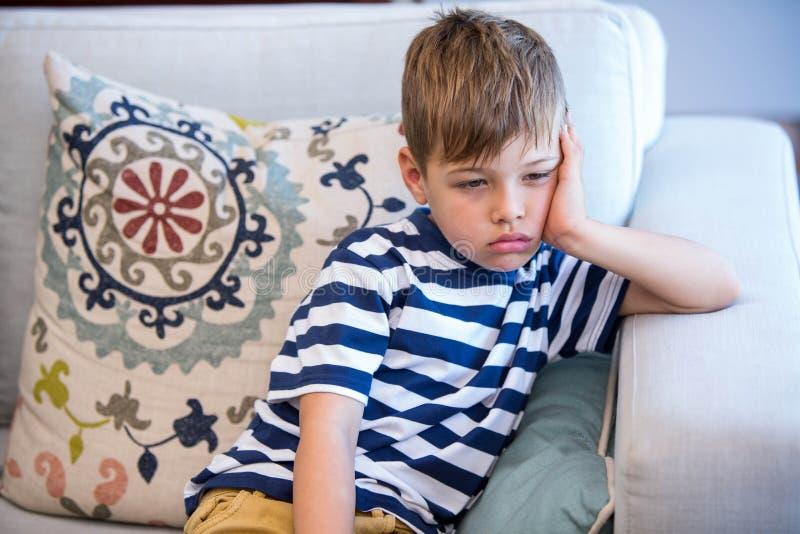 Niño pequeño cansado en el sofá fotos de archivo