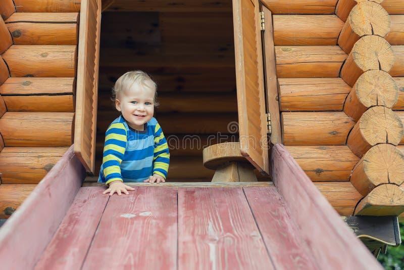 Niño pequeño caucásico adorable lindo que se divierte que desliza abajo la diapositiva de madera en el patio natural respetuoso d foto de archivo libre de regalías
