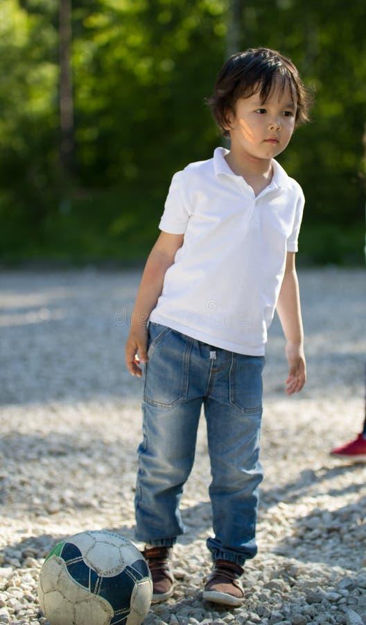 Niño pequeño caucásico lindo que juega con el balón de fútbol en el parque en el día soleado foto de archivo libre de regalías