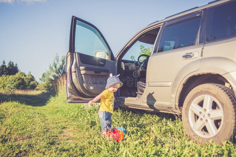 Niño pequeño cerca de jugar del coche del suv foto de archivo