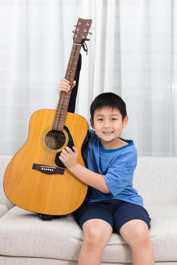 Niño pequeño chino asiático feliz que toca la guitarra en el sofá fotografía de archivo