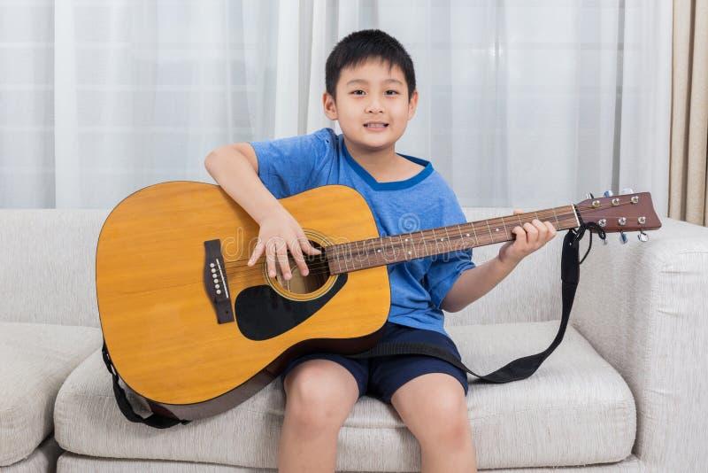 Niño pequeño chino asiático feliz que toca la guitarra en el sofá foto de archivo