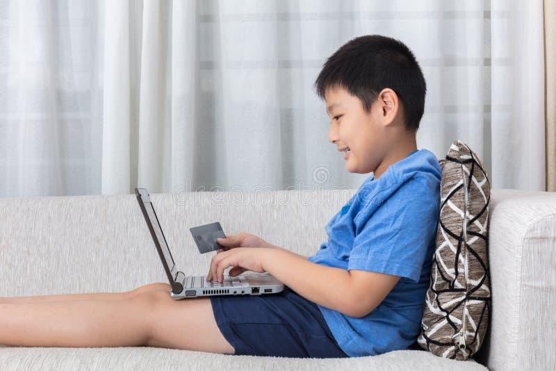Niño pequeño chino asiático feliz que usa el ordenador portátil con la tarjeta de crédito fotos de archivo libres de regalías