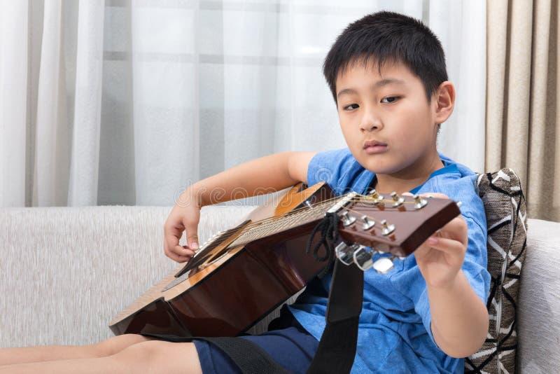 Niño pequeño chino asiático que toca la guitarra en el sofá fotos de archivo libres de regalías