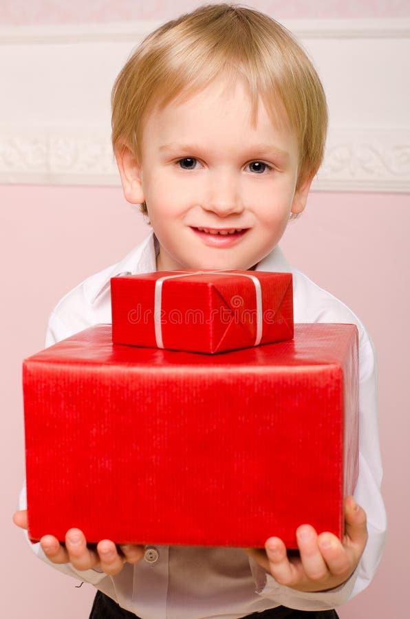 Niño pequeño con dos cajas rojas de regalos foto de archivo libre de regalías