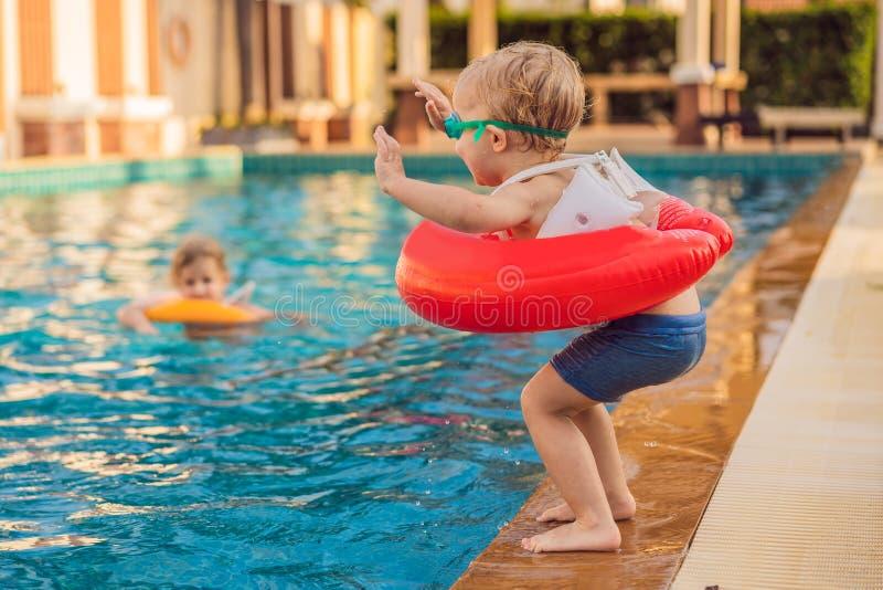 Niño pequeño con el círculo inflable en la piscina imagen de archivo libre de regalías