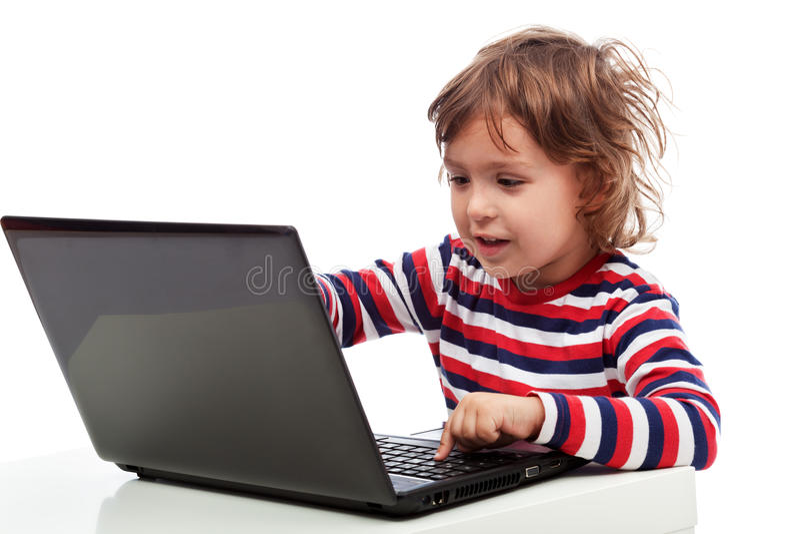 Niño pequeño con el ordenador portátil imagenes de archivo