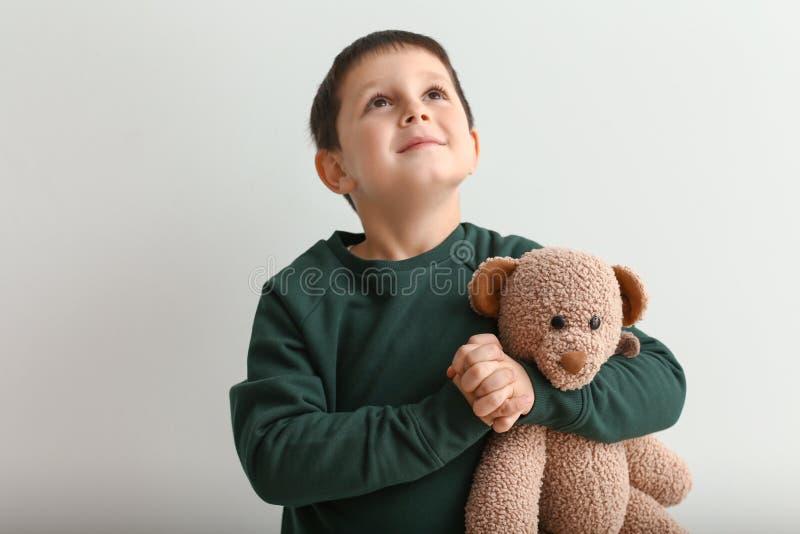 Niño pequeño con el oso de peluche que ruega en fondo ligero fotos de archivo