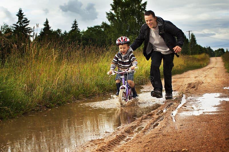 Niño pequeño con el papá en una bici después de la lluvia imágenes de archivo libres de regalías