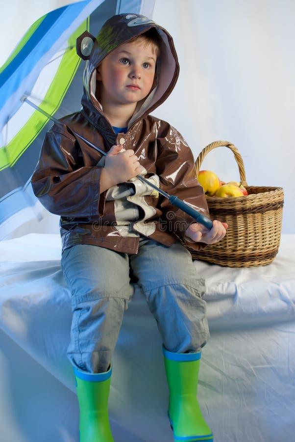 Niño pequeño con el paraguas y cesta por completo de manzanas fotografía de archivo