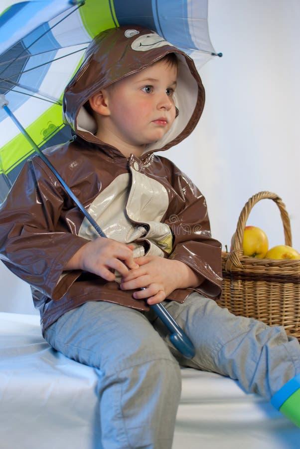 Niño pequeño con el paraguas y cesta por completo de manzanas imagenes de archivo