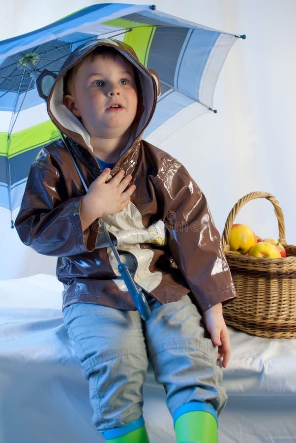 Niño pequeño con el paraguas y cesta por completo de manzanas fotos de archivo