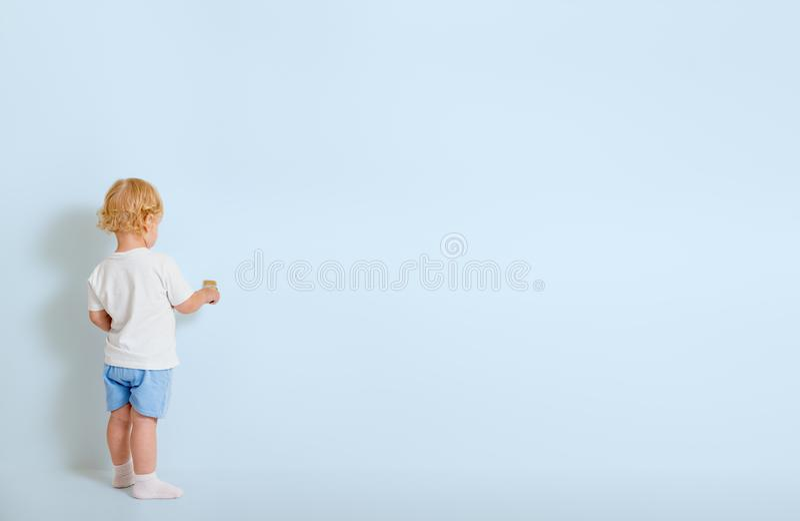 Niño pequeño con la brocha que retrocede cerca de la pared azul imagenes de archivo