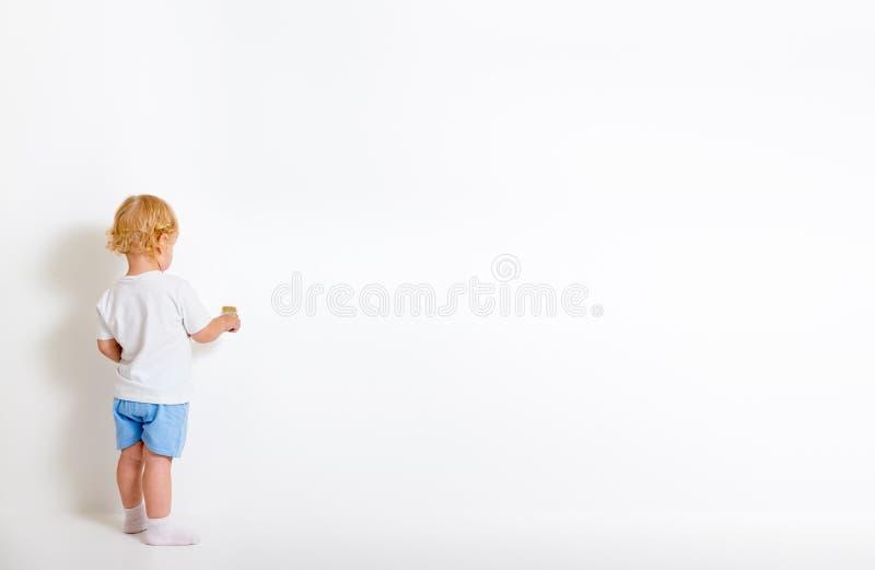 Niño pequeño con la brocha que retrocede cerca de la pared blanca fotografía de archivo libre de regalías