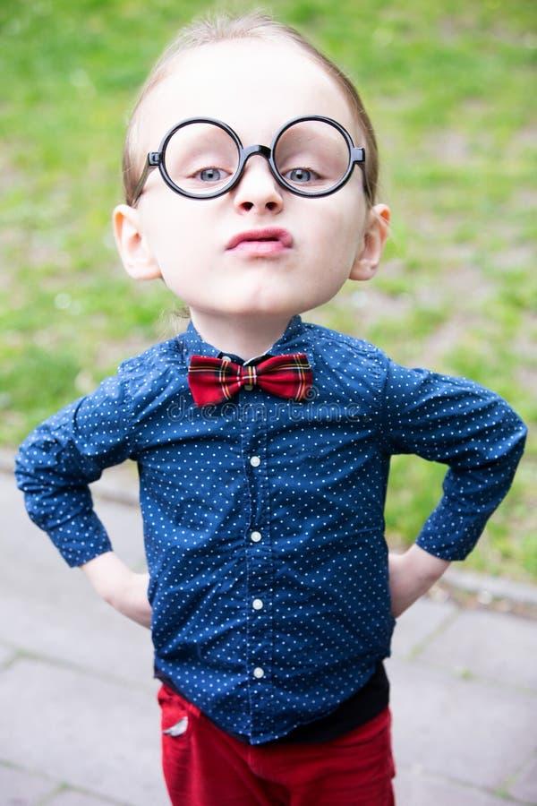 Niño pequeño con la cabeza grande y los vidrios que parecen arrogantes stock de ilustración