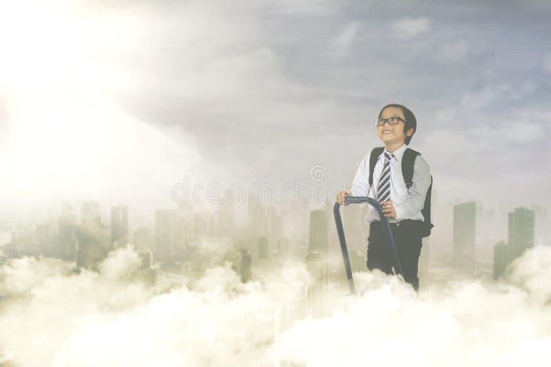 Niño pequeño con la escalera en el cielo fotos de archivo
