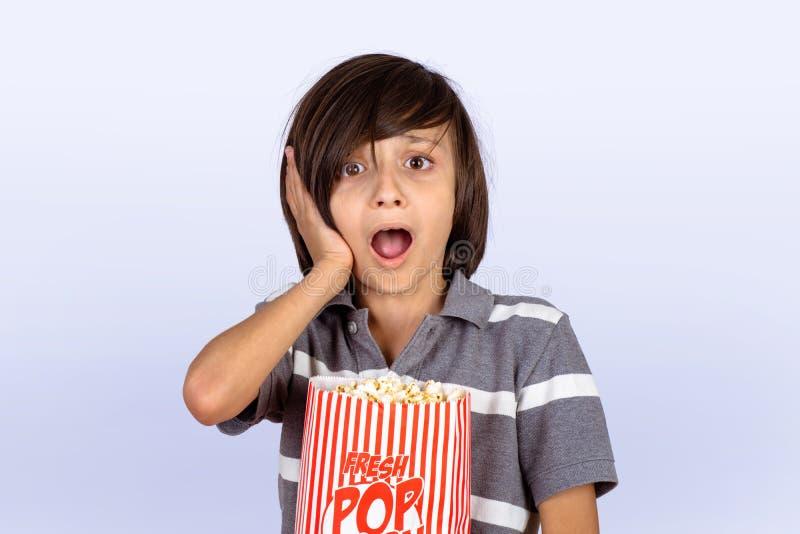 Niño pequeño con la expresión y palomitas del choque foto de archivo libre de regalías