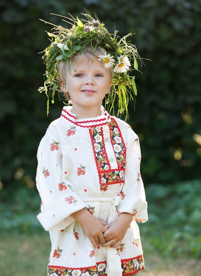 Niño pequeño con la guirnalda de la flor imagen de archivo libre de regalías