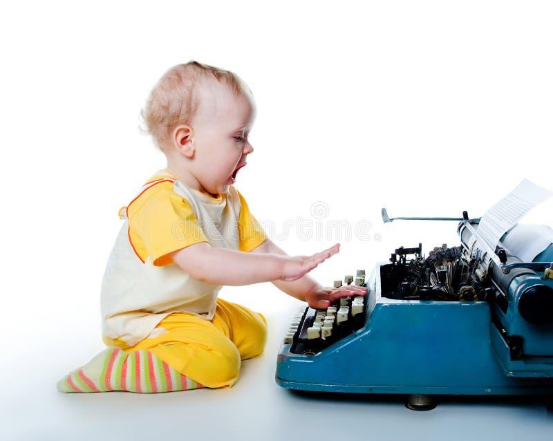 Niño pequeño con la máquina de escribir vieja imagenes de archivo
