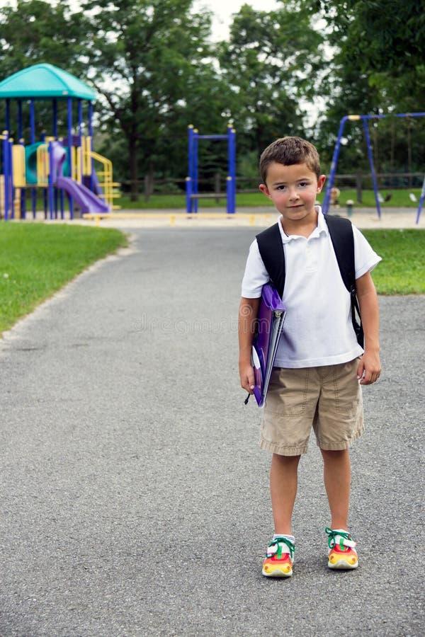 Niño pequeño con la mochila y el libro de la escuela que presentan en la yarda del juego imagen de archivo libre de regalías