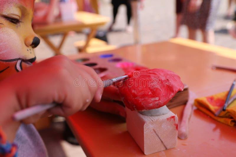 Niño pequeño con la pintura de la cara que pinta su propia obra de arte imagen de archivo libre de regalías