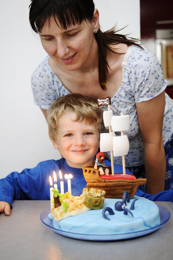 Niño pequeño con la torta de cumpleaños foto de archivo