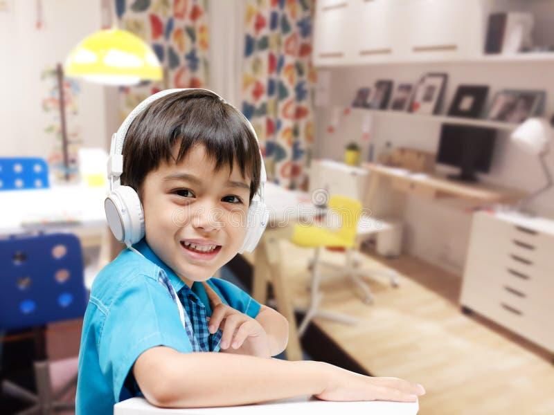 Niño pequeño con las auriculares que hacen a casa el trabajo en el cuarto imagen de archivo