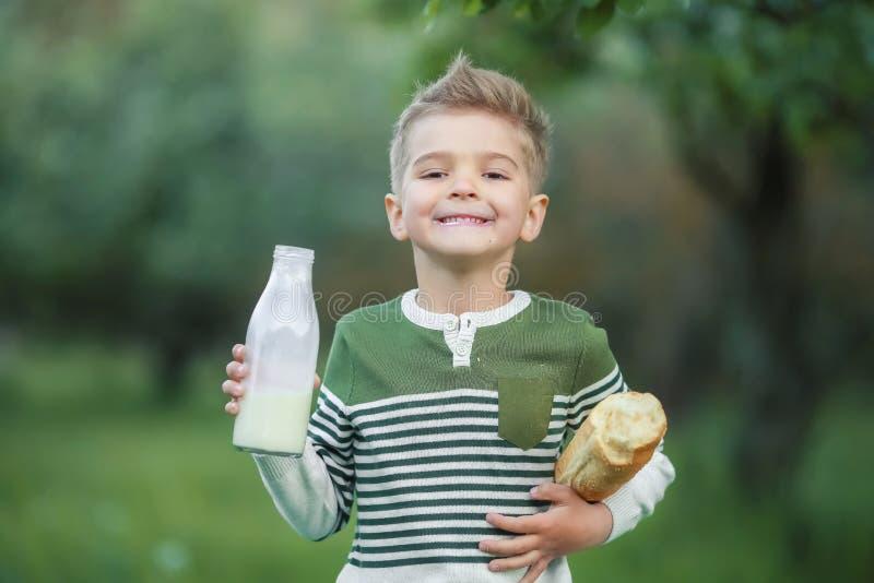 Niño pequeño con leche de la bebida de la muchacha y comer una barra de pan en un pajar en un pueblo en la puesta del sol foto de archivo libre de regalías