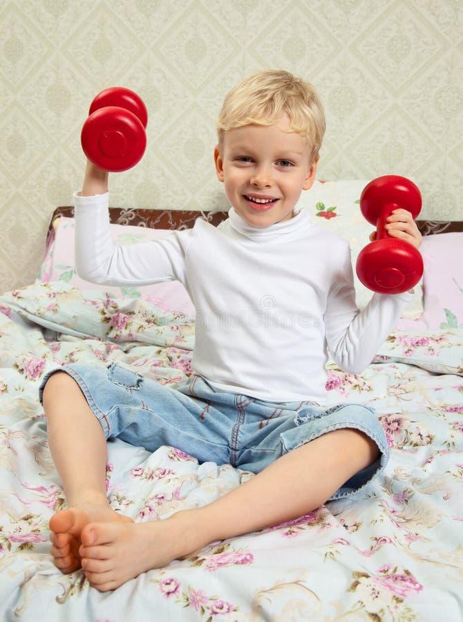 Niño pequeño con pesas de gimnasia rojas imágenes de archivo libres de regalías