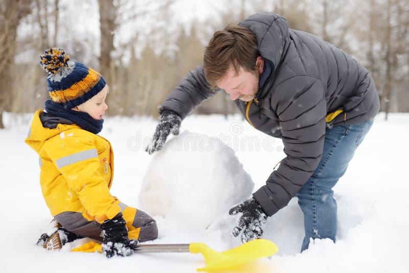 Niño pequeño con su padre construyendo muñeco de nieve en parque de nieve. Actividad al aire libre con niños en invierno imagen de archivo libre de regalías