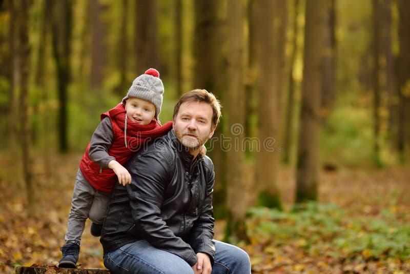 Niño pequeño con su padre durante paseo en el bosque imagenes de archivo