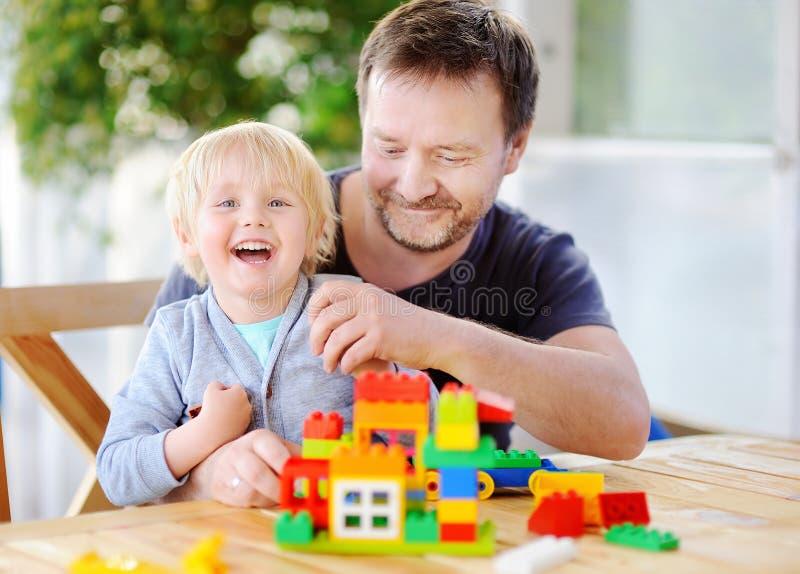 Niño pequeño con su padre que juega con los bloques coloridos del plástico en casa fotografía de archivo