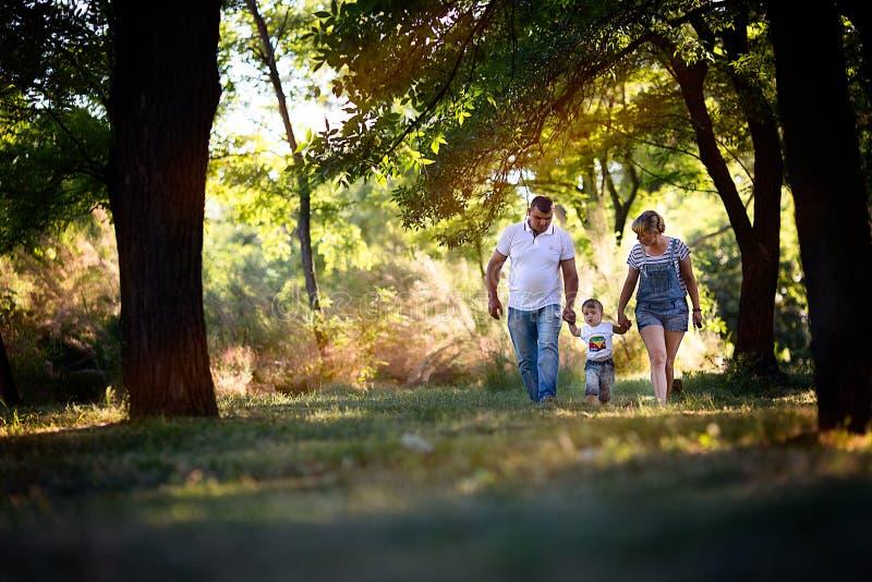 Niño pequeño con sus padres que caminan en el parque foto de archivo libre de regalías