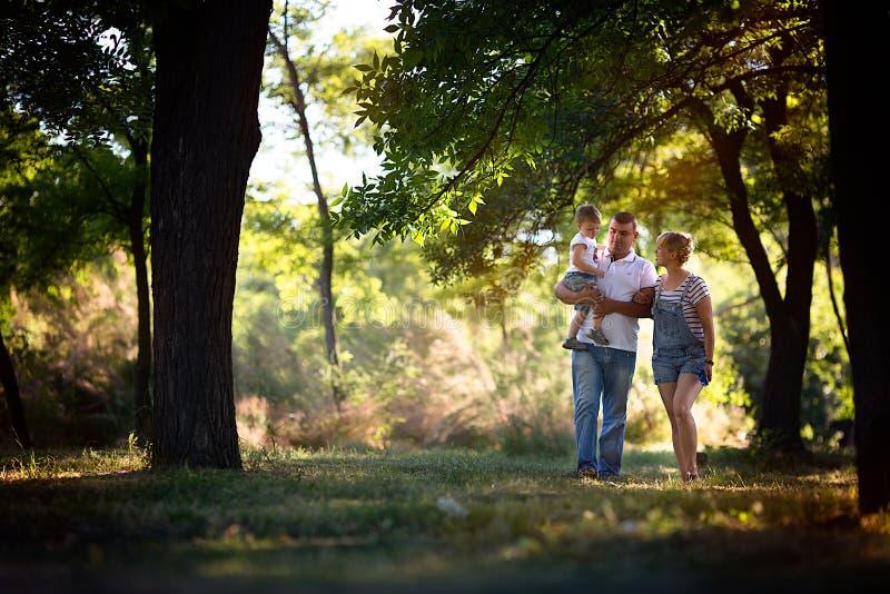 Niño pequeño con sus padres que caminan en el parque foto de archivo