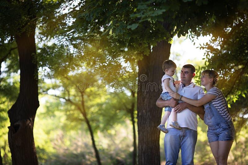 Niño pequeño con sus padres que caminan en el parque fotos de archivo libres de regalías
