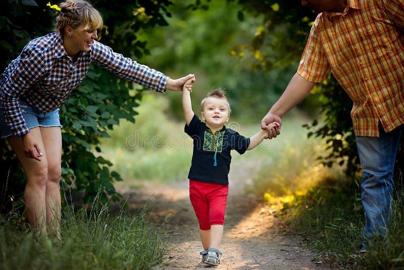 Niño pequeño con sus padres que caminan en el parque fotos de archivo