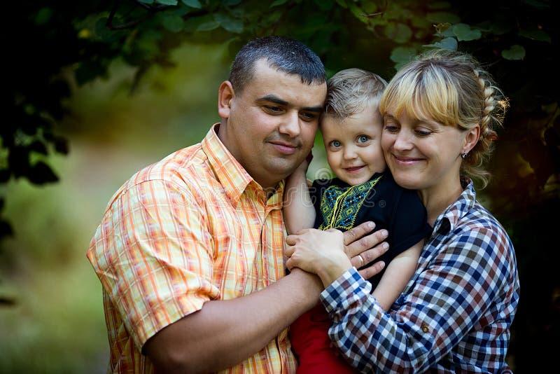 Niño pequeño con sus padres que juegan en el parque imagenes de archivo